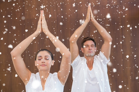 Peaceful couple in white doing yoga together with hands raised against snow falling photo