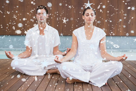 Attractive couple in white meditating in lotus pose against snow photo