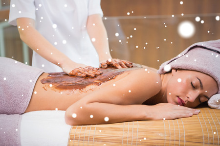 Attractive woman receiving chocolate back mask at spa center against snow photo
