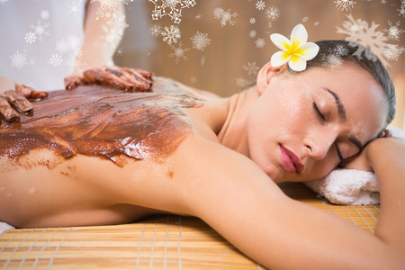 Attractive woman receiving chocolate back mask at spa center against snowflakes photo