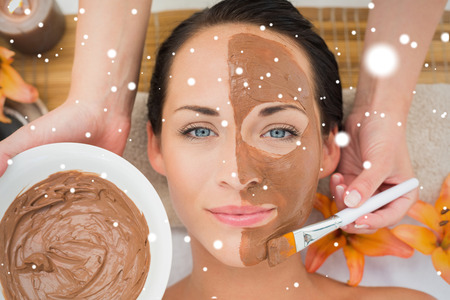 mud and snow: Peaceful brunette getting a mud facial applied against snow