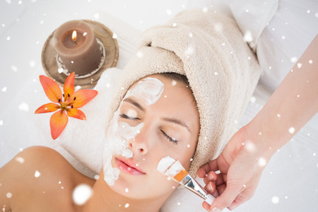 Attractive woman receiving treatment at spa center against snow falling photo