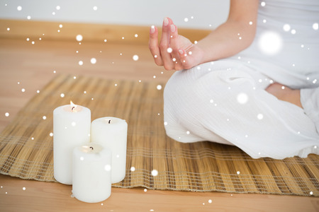 Woman sitting in lotus pose beside white candles against snow photo