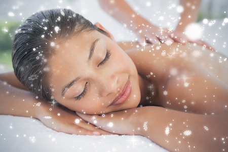 Beautiful brunette enjoying a massage  against snow falling photo
