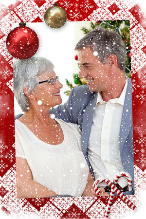 Senior couple in love in Christmas against snow falling photo
