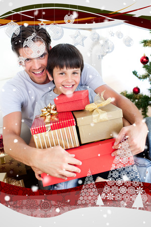 Happy father and son holding Christmas presents against snow falling photo