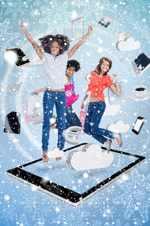 Composite image of a Three cute women jumping on a tablet pc against snow falling photo