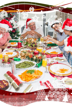 Happy family in santas hats enjoying Christmas dinner against snow falling photo