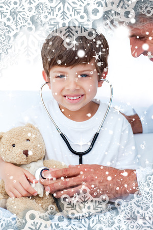 Adorable Little boy playing with his doctor  against snow falling photo