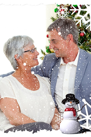 Composite image of a Senior couple in love in Christmas against snow falling photo
