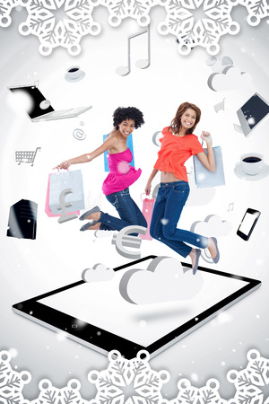 Composite image of a Two smiling women jumping on a tablet pc  against snow falling photo