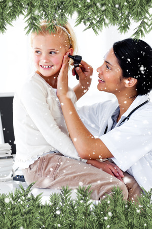 Composite image of a Cute little girl attending a medical checkup against snow falling photo