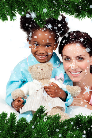 Smiling little girl with her nurse looking at the camera  against snow falling photo