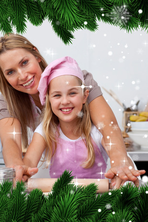 Composite image of a Mother and daughter baking Christmas cookies in the kitchen against snow falling photo