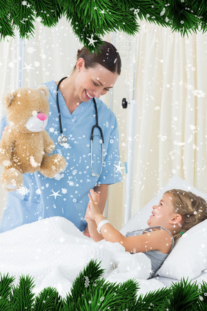 Composite image of a Playful doctor entertaining sick girl against snow falling photo