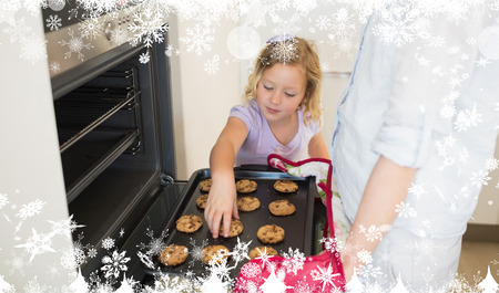 Composite image of a Girl with mother baking cookies against snow photo