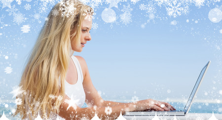 Composite image of a Pretty blonde using her laptop at the beach against snow photo