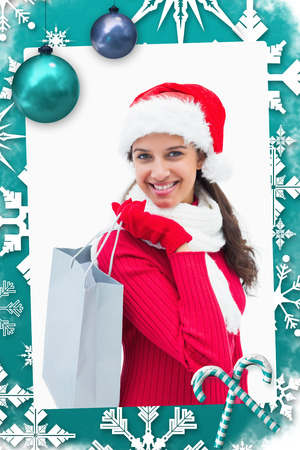 Beautiful festive woman holding shopping bag against christmas frame photo