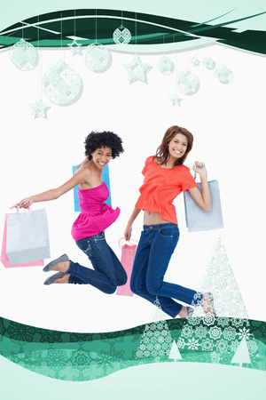 Young teenagers energetically jumping after going shopping against christmas frame