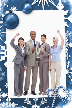 awarded: Happy business team holding a cup against christmas frame Stock Photo