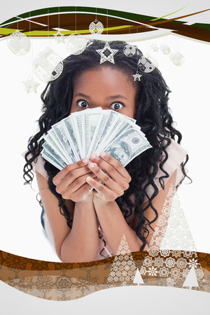 A woman is holding American dollars up to her face against christmas frame photo