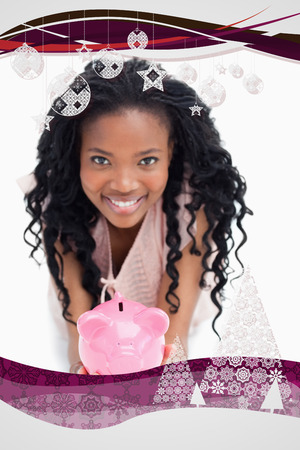 A young woman smiling at the camera is holding a piggy bank in her hands against christmas frame photo