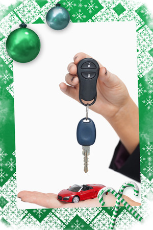 Woman holding key and small car against christmas frame photo