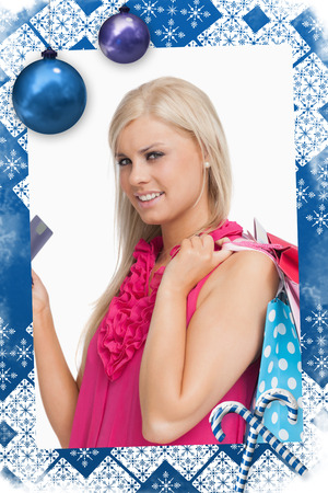 Blonde holding shopping bags and a card against christmas frame photo