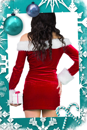 Sexy girl in santa outfit holding gift against christmas frame photo