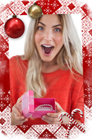 Surprised woman discovering necklace on a box against christmas themed page photo