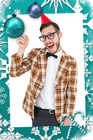 Geeky hipster in party hat pointing against christmas frame photo