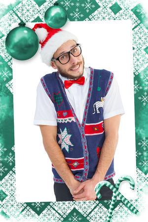 Geeky hipster in santa hat against christmas frame photo