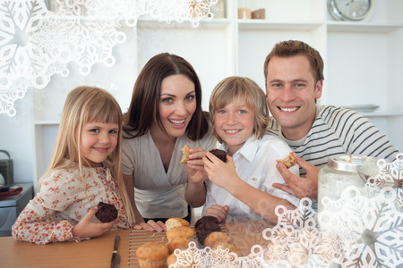 Cute children eating muffins with their parents against snowflake frame photo