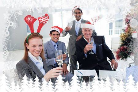 Business team toasting with Champagne at a Christmas party against fir tree forest and snowflakes photo