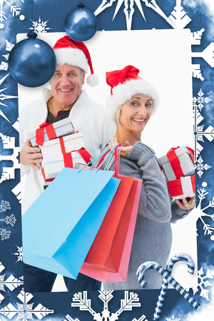 Festive mature couple in winter clothes holding gifts and bags against christmas frame photo