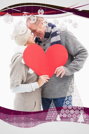 Happy mature couple in winter clothes holding red heart against christmas frame photo