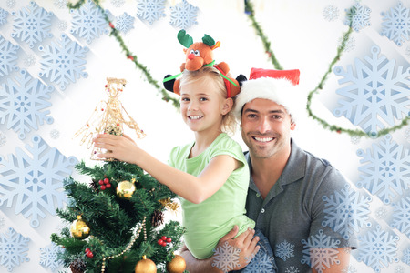 Happy father and daughter decorating together the christmas tree against snowflake frame photo