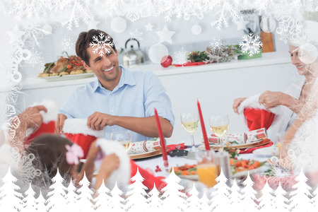 Cheerful family dining together against fir tree forest and snowflakes photo