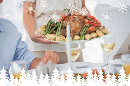 Woman brining a roast chicken in the dining room against fir tree forest and snowflakes photo