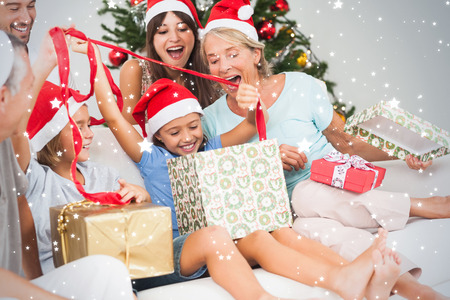 Composite image of Happy family at christmas opening gifts together against snow photo