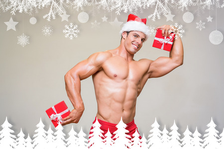 Shirtless macho man in santa hat holding gifts against fir tree forest and snowflakes