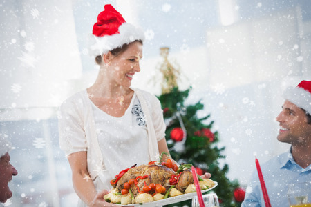 Cheerful woman wearing santa hat and bringing a roast chicken against snow photo