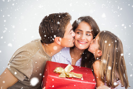 Composite image of Father and his daughter offering a red gift against snow falling photo
