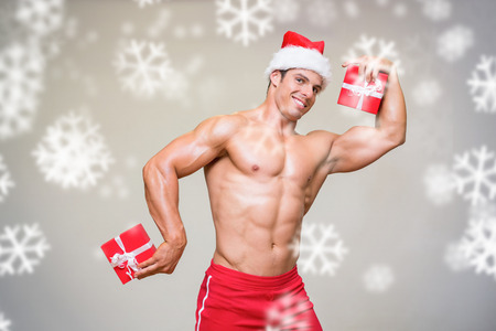 Shirtless macho man in santa hat holding gifts against snowflakes photo