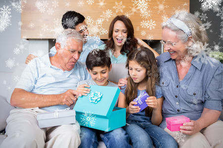 Extended family sitting on sofa with gift boxes in living room against snowflakes photo