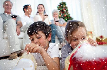 botas de navidad: Imagen compuesta de ni�os en busca de regalos en las botas de Navidad contra la nieve ca�da Foto de archivo