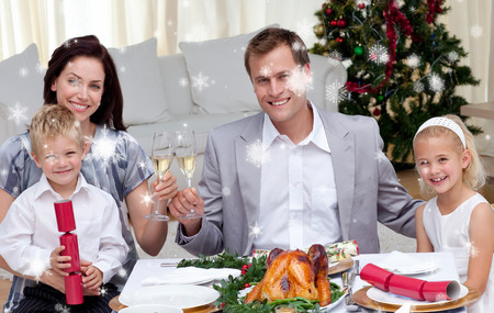 Parents toasting with wine in Christmas dinner against snow falling photo
