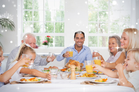 Composite image of Family toasting at thanksgiving against snow falling photo