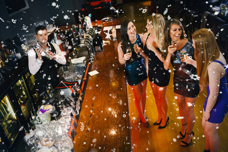 Gorgeous women having cocktails together against snow falling photo