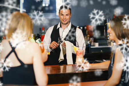 Handsome bartender working while gorgeous friends speaking against snowflakes photo